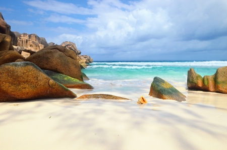 Granite rocky beaches on Seychelles islands, La Digue,Grand Anse. Big orange shell in the surf photo