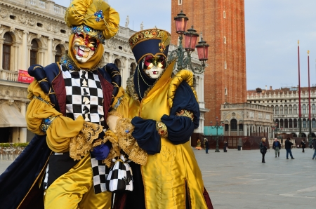 VENICE - MARCH 7: Twounidentified masked persons  in costume in St. Mark