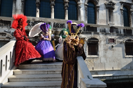 VENICE - MARCH 7: Group of  an unidentified masked persons in costume on the bridge via Venice canal during the Carnival on March 7, 2011. The 2011 carnival was held from February 26th to March 8th.