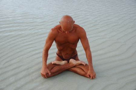 bodyscape: The tanned caucasian man is practicing yoga on the beach