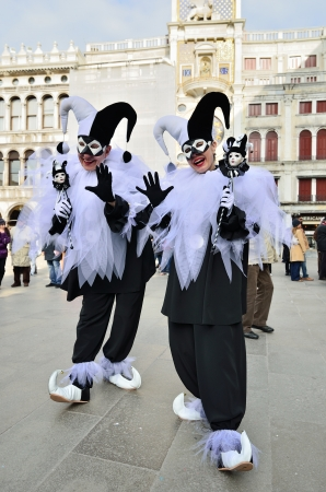 VENICE - MARCH 7: Two unidentified masked persons in Arlekino costume in St. Mark