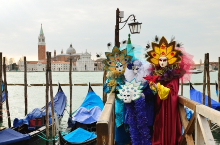 VENICE - MARCH 7: Three unidentified masked persons in costume in St. Mark's Square during the Carnival of Venice on March 7, 2011. The 2011 carnival was held from February 26th to March 8th. Stock Photo - 14050363
