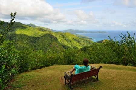 Girl sit on a bench and looks at the mountains and the ocean, Seychelles islands, Mahe photo