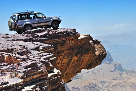 extreme terrain: Over land. Lone car is standing on the rock over breakaway Stock Photo