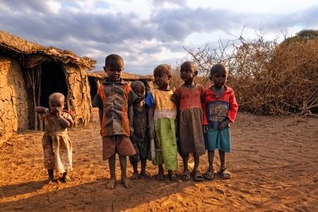 niños africanos: Masai Mara, Kenya - 23 de agosto: Los niños pequeños no identificados de Masai de Kenia tribu vestida con ropa sencilla y sucios 23 de Ago de 2010 en Masai Mara, uno de los famosos parques de la reserva nacional en Kenia