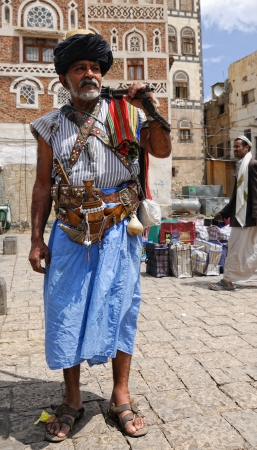 Unidentified old man shown in the capital of Yemen Sanaa on March 6, 2010. Armed man in traditional costume with typical arme blanche jambia stands with ancient rifle on the street.