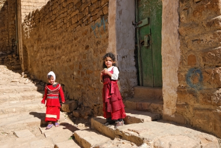 arab girl: YEMEN, THULA – MAR13:Two unidentified Yemeni girsl with candy donated by tourists near door of family house, Thula, Yemen March 13, 2010. Nearly half of Yemeni children are at risk of malnutrition Editorial