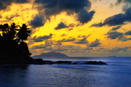 Silhouette of palm tree and islands in the Indian ocean at sunset, Seychelles, Mahe