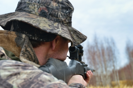Armed hunter in camouflage uniform with a gun in autumn forest Imagens