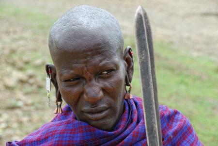 tribu: Serengeti, Tanzania, 22 de enero: Un hombre no identificado guerrero africano en el vestido tradicional de la tribu Masai se muestra en la sabana en el Parque Nacional del Serengeti en enero de 2008