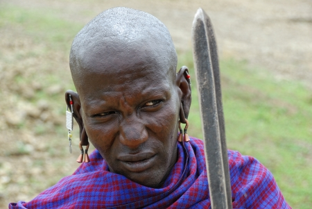 SERENGETI, TANZANIA, JAN 22: An unidentified African warrior man in traditional dress from Masai tribe shown in the savannah in the Serengeti National park on January, 2008