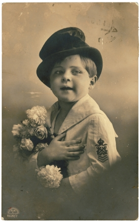 depicts: RUSSIA - CIRCA 1906: Retro postcard with weathered edges on white background printed in circa 1906, Russia. Vintage hand-tinted photograph depicts a young boy with bouquet of flowers