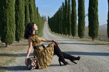 Place of destination  Stylish young woman sits on the suitcase on a rural road along cypress alley  Tuscan, Italy photo