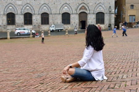 Tired young tourist girl sits on the medieval square of Siena  Italy  photo
