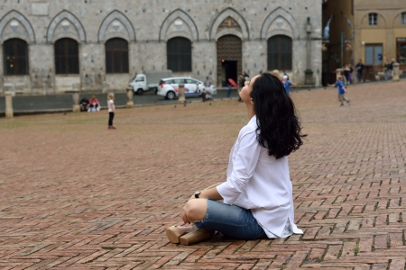 Young tourist gir sits on the medieval square of Siena  Italy photo