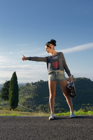 Stylish attractive young woman hitchhiking along a road  Tuscan, Italy photo