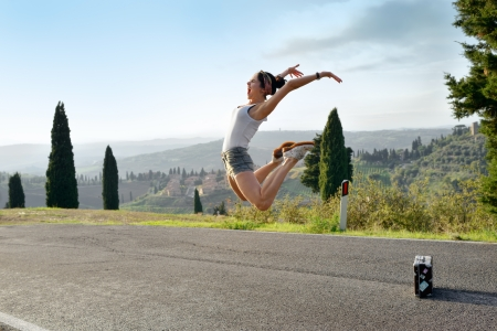 Home leave  Beautiful young girl in delight jumping high in the air on a rural road in Tuscan, Italy  Warm evening light photo