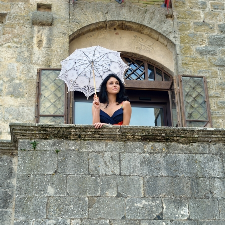 Beautiful sensual young girl with white umbrella standing on the stone balcony of the old medieval castle near open window, Tuscan, Italy photo