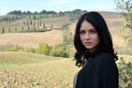 Portrait of a calm young woman with bright blue eyes on idyllic Tuscan landscape background  Italy Imagens