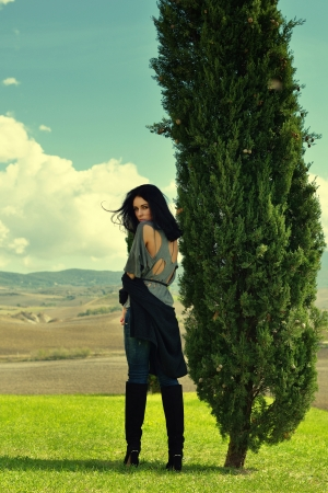 Beautiful young woman standing near cypress on green meadow in the sunny day in the country, Tuscan, Italy  Cross processing image  photo