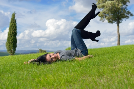 Beautiful young woman is lying on green meadow on sunny day in the country, Tuscan, Italy  photo