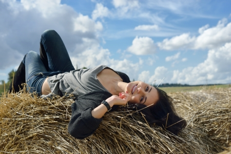 Beautiful young woman is lying on stack of hay on sunny day in the country photo