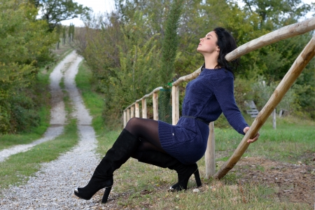 Beautiful calm young woman is posing in the country early autumn time, Tuscan, Italy photo