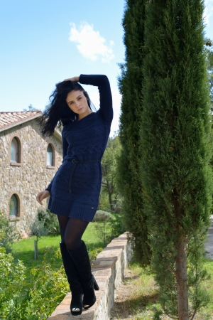 Beautiful calm young woman standing on the stone fence of the old farmhouse, Tuscan, Italy Imagens