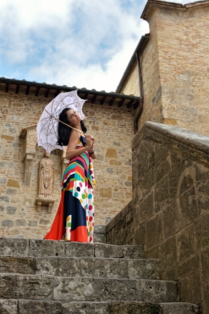 stilish: Beautiful stilish young woman with umbrella standing near the stone tower of the old castle, Tuscan, Italy