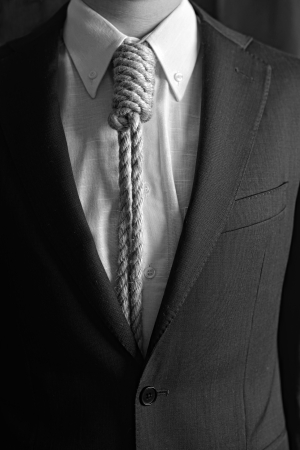 Detail of businessman with hangman noose instead of tie symbolizing economic problems Stock Photo
