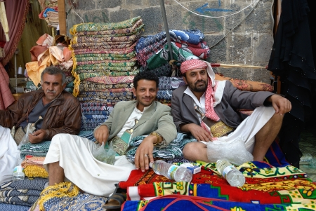 suq: SANAA, YEMEN - MARCH 6: Three unidentified men sell carpet on Mar 6, 2010 in Sanaa, Yemen. Open markets play a central role in the social-economic life of one of the poorest countries in the Arab World