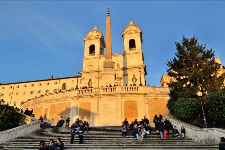 spanish steps: ROME - MARCH 10: Tourists sit on the Spanish steps with Santissima Trinita dei Monti church at the top in Rome on Mar 10, 2011. The Spanish Steps are the widest staircase in Europe