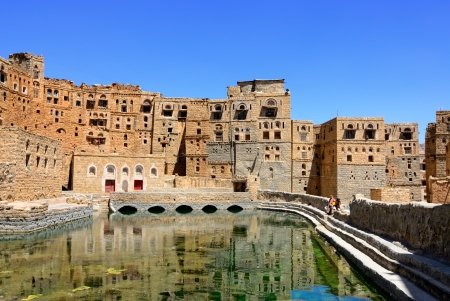 basin mountain: Traditional architecture in mountain village Habbabah with public fountain basin, Yemen Stock Photo