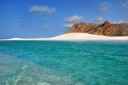 Azure water and white sand dune. A sandy coastline and a colorful lone cliff at the sunset, Socotra island, Yemen Imagens