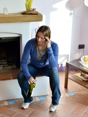 Attractive woman in living room with empty bottle of red wine
