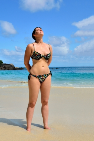 indian sexy: Young tanned girl stands at the sandy beach and is taking a sunbath against azure ocean and bright blue sky. Tropical vacation