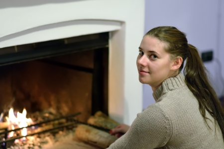 Portrait of young girl near fireplace photo