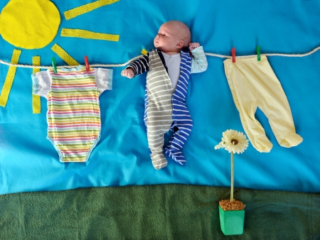 Panels with a baby. Cute 1,5 month old Caucasian baby boy among drying clothes on a rope under bright sun beam Stock Photo