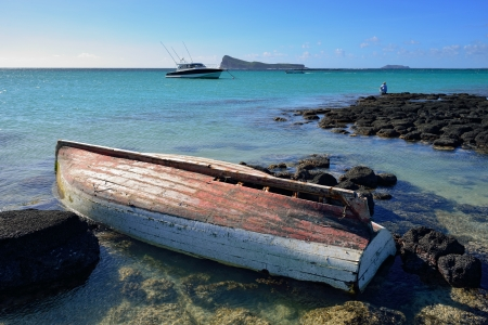 Old fishing boat on the rocky shore of Mauritius island. View on the Coin de Mire island photo