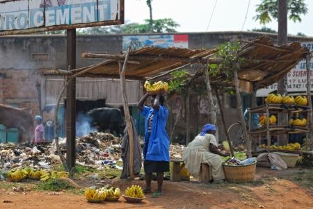 KAMPALA, Oeganda - 26 augustus: Inheemse mensen verkopen bananen op de lokale markt op 26 aug 2010 in sloppenwijk van Kampala, Oeganda. Bijna 40% van de sloppenwijkbewoners hebben een maandelijks inkomen van slechts 2.500 shilling - minder dan een dollar, 98% van hen is vrouw Redactioneel
