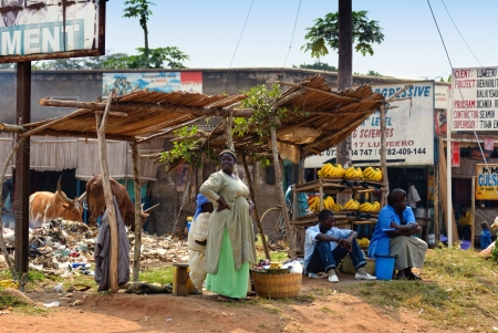 slum: KAMPALA, UGANDA - AUG 26: Native people sell banana at local market on Aug 26, 2010 in slum of Kampala, Uganda. Nearly 40% of slum dwellers have a monthly income of just 2,500 shillings – less than a dollar,  98% of those are women