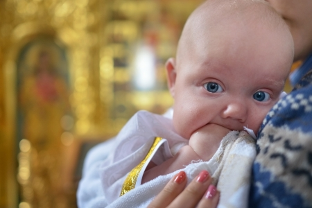 A portrait of a baby boy on the mother hands in a christening dress on a golden background of church. This photo has a shallow depth of field and the focus is on his eye Imagens