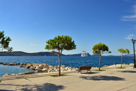 View on Navarino bay from Pylos, luxury cruise ship, bench and trees on seafront  Greece Imagens
