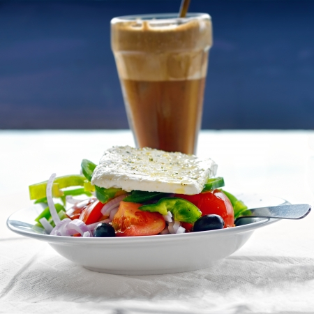 Traditional greek vegetarian cuisine  Salad with feta cheese, greek olives and glass of frappe