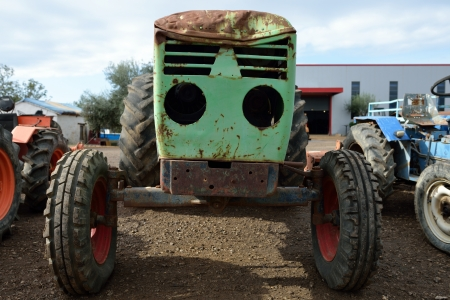 Old wrecked rusty tractor on a junkyard photo
