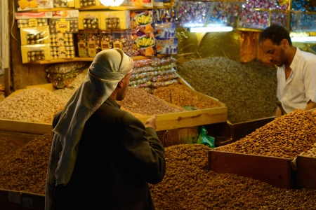 suq: SANAA, YEMEN - MARCH 6, 2010  Unidentified man buys nuts at the night market  Open markets play a central role in the social-economic life of one of the poorest countries in the World