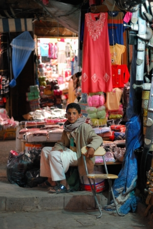 suq: SANAA, YEMEN - MARCH 6, 2010  Unidentified young boy sells the goods at the night market  Open markets play a central role in the social-economic life of one of the poorest countries in the World