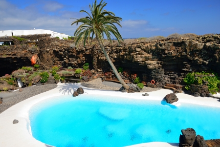 Blue swimming pool in tropical garden inside of lava cavern, Lanzarote