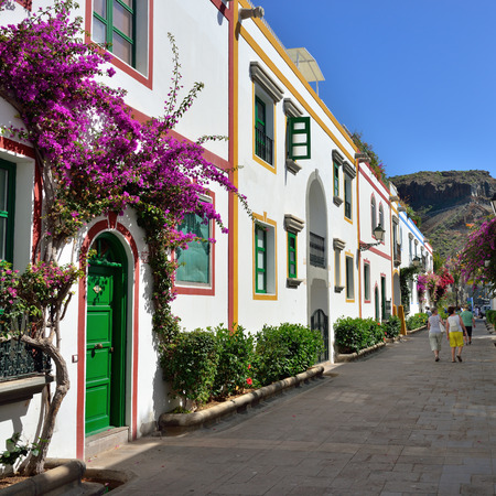 Street with white houses colonia shown in Puerto de Mogan, Spain   Favorite vacation place for tourists and locals on island