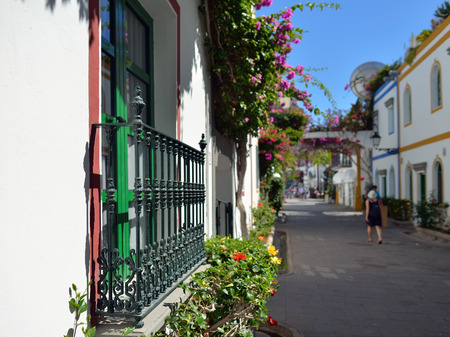 Street with white houses colonia shown in Puerto de Mogan, Spain   Favorite vacation place for tourists and locals on island  Focus on the balcon